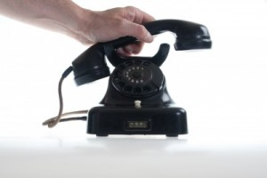 MAle hand picking up antique phone